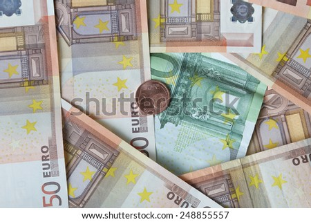 Euro banknotes of fifty and one hundred denomination with five cents coin lies over them - money concept and financial background - stock photo