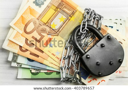 Euro banknotes with lock and chain on wooden table background - stock photo