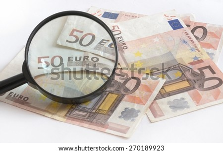 Euro banknotes with magnifying glass - stock photo