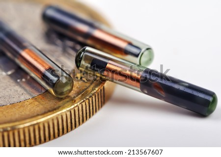 Euro cent near animal implants for comparison - stock photo