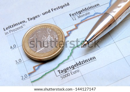 Euro coin and ball pen on a light blue colored money investment chart - stock photo