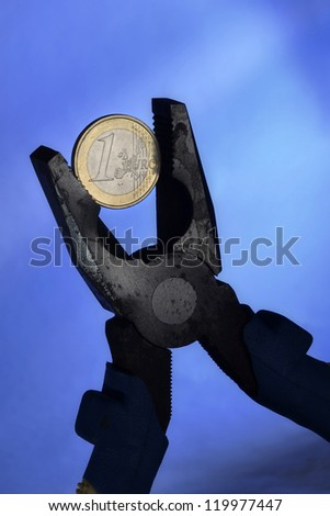 Euro coin and pliers symbolizing the European Union economic depression and the European currency under pressure - stock photo
