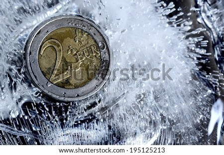 euro coin frozen in ice cube - stock photo