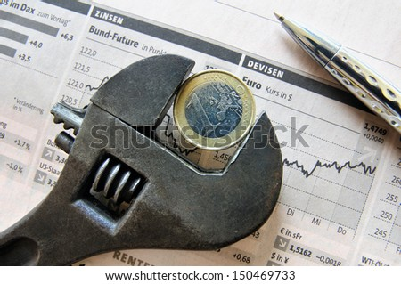 Euro coin in an adjustable wrench on top of a stock market report - stock photo