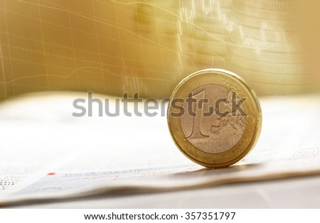 Euro coin on stock chart with shallow depth of field - stock photo