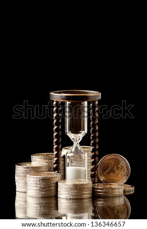 EURO coins and hourglass on black background. Studio shot. - stock photo