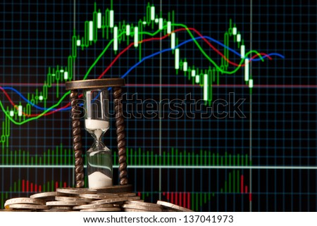 EURO coins and hourglass with forex trading bars on background. Studio shot. - stock photo