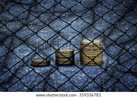 Euro coins, cracks and fence - Finance concept - stock photo