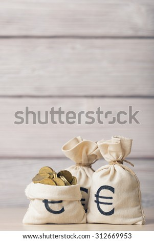 Euro coins in money bag over defocused wooden background - stock photo
