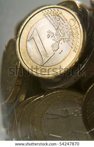 Euro coins in piggy bank glass - stock photo