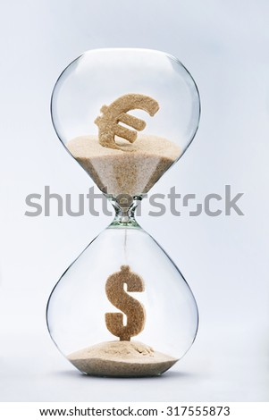 Euro-dollar exchange rate. Dollar sign made out of falling sand from euro sign flowing through hourglass - stock photo