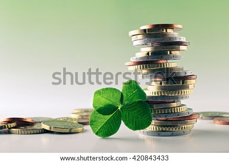 Euro money closeup coins,stacked on each other in different positions background green,Four Leaf Clover for luck. - stock photo