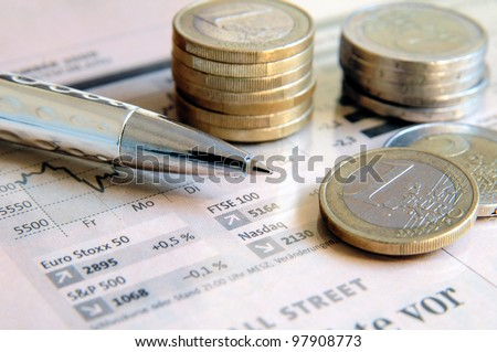 Euro money coins and silver colored ball pen on a light pink colored stock market report - stock photo