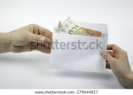 Euro notes in an envelope being handed from one person to another. - stock photo