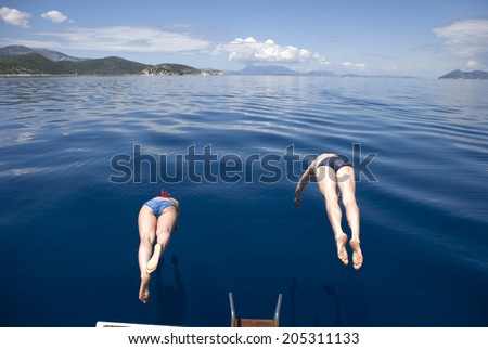 Europe, Greece, Ionian, Mediterranean Sea. The synchronous jumps in the sea from the yacht. - stock photo