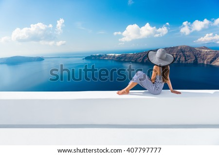 Europe Greece Santorini travel vacation. Woman looking at view on famous travel destination. Elegant young lady living fancy jetset lifestyle wearing dress on holidays. Amazing view of sea and Caldera - stock photo