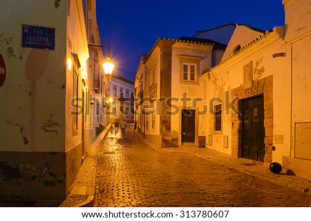 Europe, Portugal, Faro - Street view of the historical old town at dusk - with street name and city very old coat of arms symbol - stock photo