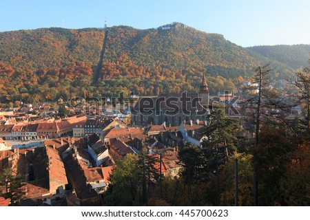 Europe, Romania, Brasov, Council Square, Piata Sfatului, clock tower, Brasov historical Museum. Black Church as seen from hillside overlooking city signage on Tampa Mountain. - stock photo