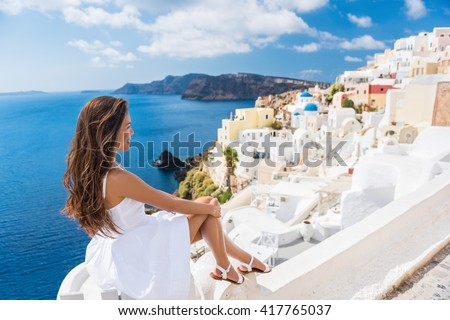Europe summer travel destination Santorini tourist woman on vacation relaxing. Asian girl in white dress visiting the streets of the famous white village Oia with the mediterranean sea and blue domes. - stock photo