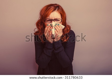 European appearance woman in glasses haired handkerchief on a gray background, disease, rhinitis retro - stock photo