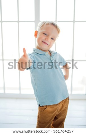 European boy in blue shirt  making thumbs up - stock photo