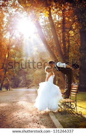 European bride and groom kissing in the park - stock photo