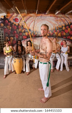 European capoeira performers with group playing music indoors - stock photo