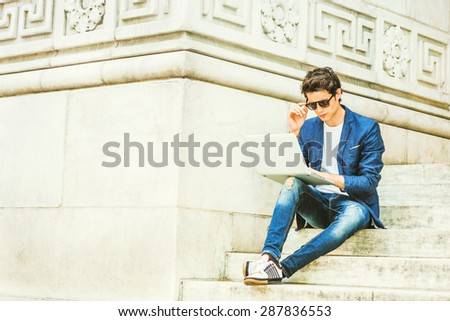 European college student studying in New York. Wearing blue blazer, jeans, sneakers, sunglasses, young guy sitting on stairs on campus, reading, thinking, working on laptop computer. Instagram effect. - stock photo