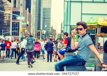 European college student traveling in New York. Wearing blue pattered short sleeve shirt, holding sunglasses, a guy sitting on street, thinking. Many people on background. Instagram filtered look.  - stock photo