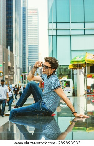 European college student traveling in New York. Wearing blue pattered short sleeve shirt, jeans, holding sunglasses, young guy sitting on marble stage on street, thinking. Many people on background.  - stock photo