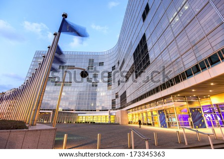 European comission building in dusk with flags waving - stock photo