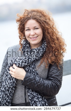 European curly hair woman looking at camera while standing on wind - stock photo