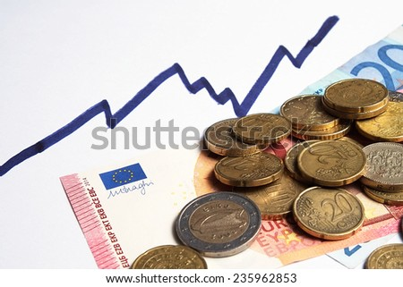European currency with a rising financial chart line above. Paper money and coins - stock photo