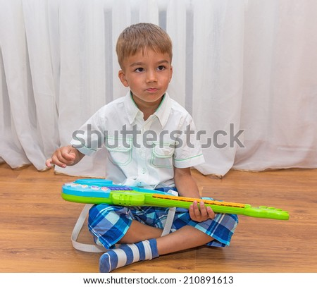 European cute boy sitting on the floor and playing a toy guitar - stock photo