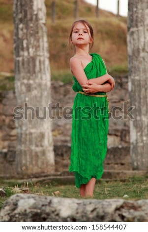European cute young girl with a charming smile in vintage dress on a background of the excavation of ancient Greek city - stock photo