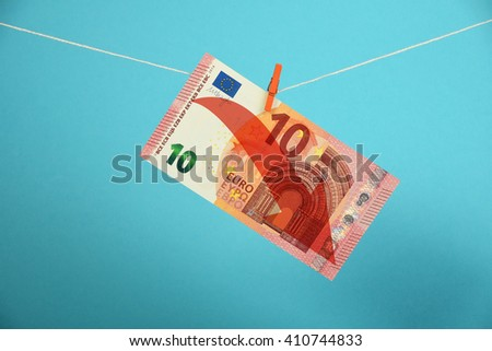 European economy crisis, decline of Euro, ten Euro banknote with red arrow down hanged descending with pin at rope over blue background - stock photo
