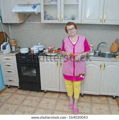 European elderly woman in the kitchen is a full-length with a knife in his hand on a background of kitchen equipment - stock photo