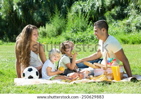 European family with little children having picnic in park - stock photo