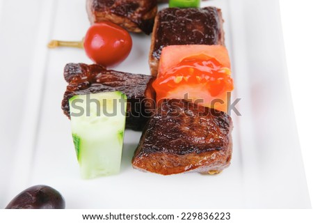 european food: grilled meat goulash on white plate with raw tomato, dill and olives . shallow dof - stock photo