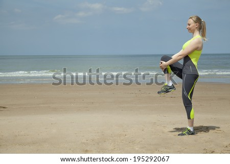 European girl in green sports suit doing stretching exercises on the beach - stock photo