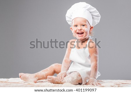 European laughing girl in chef hat and in pinafore knead the dough from flour. Little laughing girl chef holding a rolling pin for rolling dough.  - stock photo