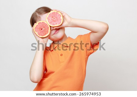 European little gil holding delicious grapefruit - stock photo