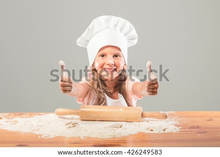 European little girl in chef hat and in pinafore knead the dough from flour. On the table is scattered flour and a rolling pin is for test. The child laughs and shows Like. - stock photo