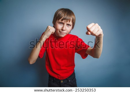 European-looking boy of ten years shows a fist, anger, threat on a gray background - stock photo