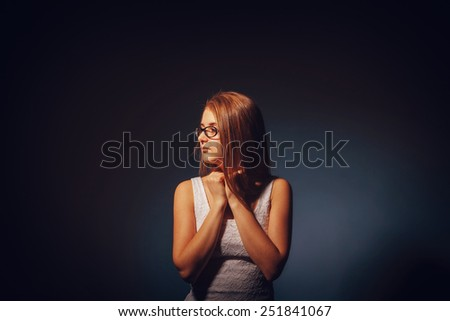 European-looking girl of twenty years of sadness, loneliness on a gray background retro - stock photo