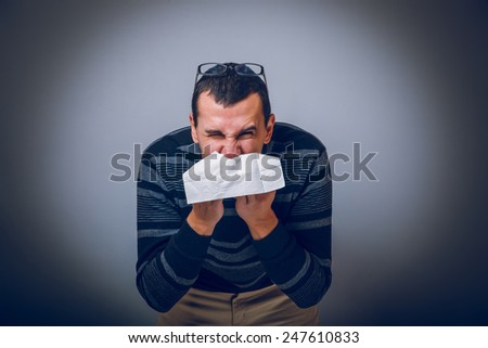 European-looking male of about thirty brunet blowing his nose into a handkerchief on a gray background, runny nose cross process - stock photo