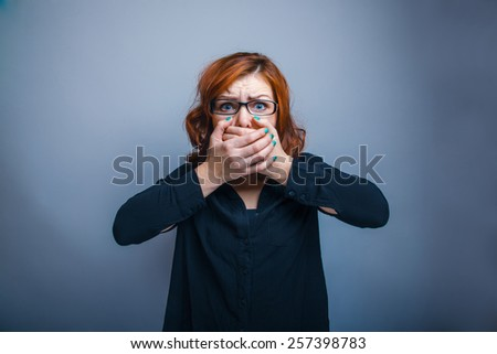 European-looking woman of thirty years in glasses, closed his mouth with his hand, fear on a gray background - stock photo