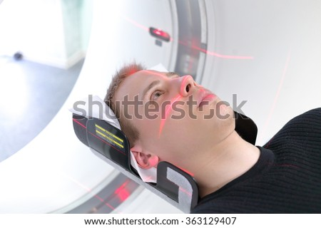 European man are entering brain with CT scan in hospital room - stock photo