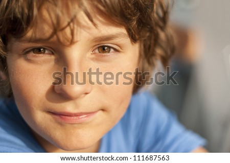 European school-age boy with brown eyes looking directly at the camera, close-up - stock photo