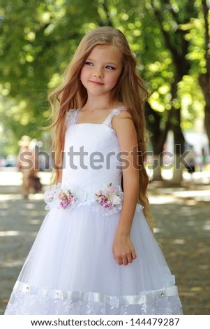 European smiling cute girl with long hair in a white wedding dress in a summer park outdoors - stock photo